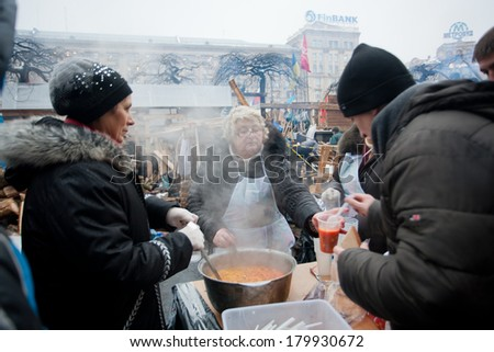 KIEV, UKRAINE - DEC 12: Elderly women cook traditional soup & distribute people on the street during Euromaidan protest on December 12 2013. More 800,000 protesters participated in Kiev Euromaidan - stock photo