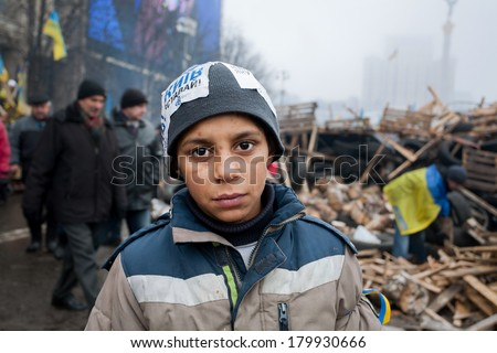 KIEV, UKRAINE - DEC 12: Unidentified homeless boy play on the cold street during anti-government Euromaidan protest on December 12 2013. More than 800,000 protesters participated in Kiev's Euromaidan - stock photo