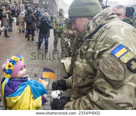 "KIEV, UKRAINE - December 6, 2014: Little girl in the Ukrainian flag gives a toy soldier from the ""Kiev 12"" volunteers battalion on the main street Khreschatyk.  - stock photo"