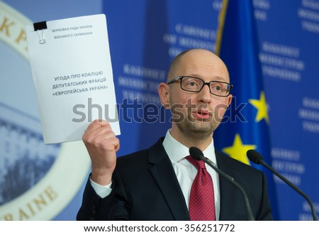 KIEV, UKRAINE - DECEMBER, 29, 2015: Prime-minister Arsenii Yatseniuk holds a copy of the coalition agreement of the parliamentary parties during press conference - stock photo