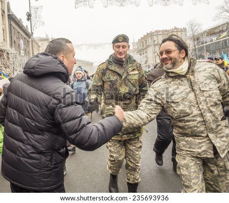 "KIEV, UKRAINE - December 6, 2014: Residents of the city welcomed the soldiers from the ""Kiev 12"" volunteers battalion are going on the main street Khreschatyk."