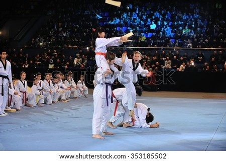 KIEV, UKRAINE - DECEMBER, 16, 2015: Ukrainian Combat Games III - nationwide Combat Games - young athletes demonstrate the group technique - in flight breaks plywood panel - stock photo