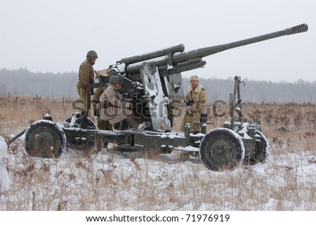 KIEV, UKRAINE - FEB 20: Members of military history club wear historical Soviet uniform& air defense cannon during historical reenactment of WWII,,February 20, 2011 in Kiev, Ukraine - stock photo