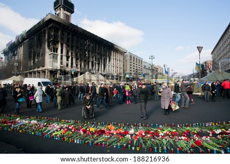 KIEV, UKRAINE - FEB 24: People with flowers ?ame past burnt building to honor the memory of 100 people were killed on the street during civil and anti-Russian protest on Fabruary 24, 2014, in Kyiv.  - stock photo