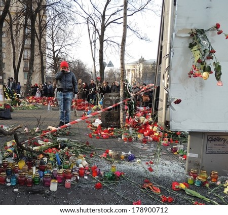 KIEV, UKRAINE - FEB 26, 2014: Woman cry on the covered with flowers street, where dozens protesters were killed.