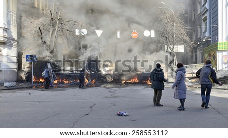 KIEV UKRAINE FEBRUARY 18, 2014: Day of mass shooting of Euromaydan protesters. The unarmed participators of march of resistance on Institutska street looks at armed special forces behind flaming cars