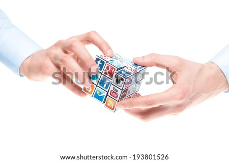 KIEV, UKRAINE - FEBRUARY 2, 2013: Male hands holding Rubik's cube with logotypes of well-known social media brands. Include Facebook, YouTube, Twitter, Google Plus, Instagram, Flickr and other logo. - stock photo