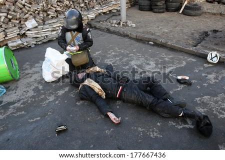 KIEV, UKRAINE - FEBRUARY 18, 2014: Military doctor provides medical care to the injured person. Kiev, Ukraine, Kiev, 18.02.2014 - stock photo