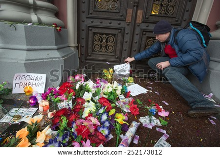 KIEV, UKRAINE - FEBRUARY, 12, 2015: Participants in the rally near the National Bank of Ukraine symbolically bury the national currency - the hryvnia, which has suffered from the devaluation - stock photo