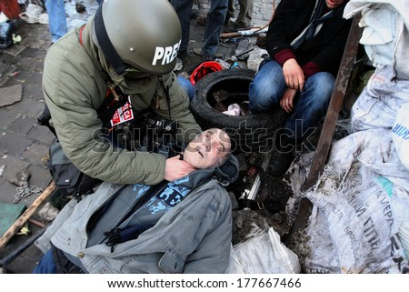 KIEV, UKRAINE - FEBRUARY 18, 2014: Photojournalist checks the pulse of a dead protester. Barricades near Khreschatyk Metro. Kiev, Ukraine, street Institutskaya. February 18, 2014