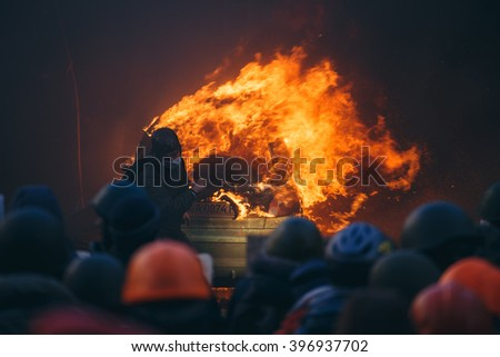 Kiev, Ukraine - 18 February 2014: Protesters burns the car to restrain the riot police and make a lot of smoke for reduced visibility, because the police shoot at protesters. Ukraine revolution. - stock photo