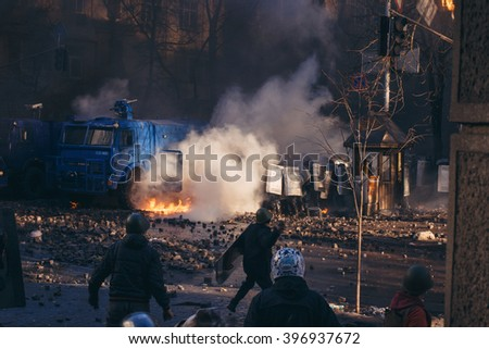 Kiev, Ukraine - 18 February 2014: ukrainian protesters trying to burn water cannon and throwing cobblestones at riot police to stop them. During violent confrontation on Instytutska Street.  - stock photo