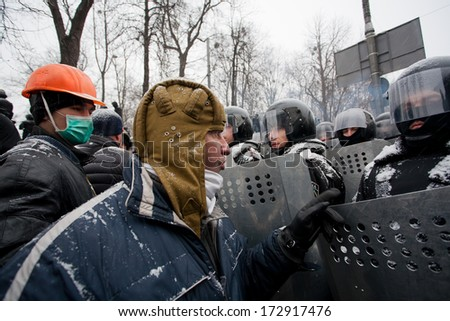 KIEV, UKRAINE - JAN 21: Angry protester in a military helmet arguing with policemen in government quarter during winter anti-government protest Euromaidan on January 21, 2014, in Kyiv, Ukraine.  - stock photo