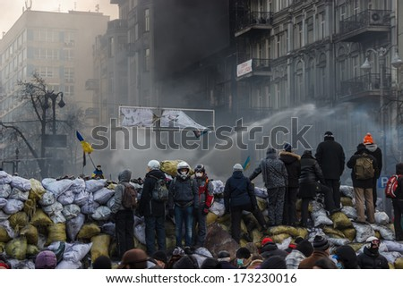 KIEV, UKRAINE - JAN 25, 2014: Confrontation on the street Hrushevskoho. Riot police extinguish burning tires from the jet. And at the same time is watering demonstrators at 14 degrees below zero