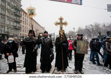 KIEV, UKRAINE - JAN 21: Group of priests of Ukrainian Orthodox Church stand with icons and big crosses on the winter street during anti-government protest on January 21, 2014, in center of Kyiv.  - stock photo