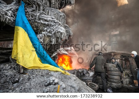 KIEV, UKRAINE - JAN 25, 2014: Mass anti-government protests in the center of Kiev. Protesters burn tires in the conflict zone on the Hrushevskoho St.  - stock photo