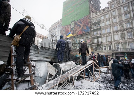 KIEV, UKRAINE - JAN 21: Men wait for attack and watch out police squad behind the barricades with metal scrap during anti-government protest Euromaidan on winter street on January 21, 2014, in Kiyv - stock photo