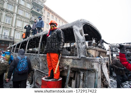 KIEV, UKRAINE - JAN 21: Protester with a baton and a helmet look out the burned street near the big military automobile during anti-government protest Euromaidan on January 21, 2014, in Kyiv, Ukraine - stock photo