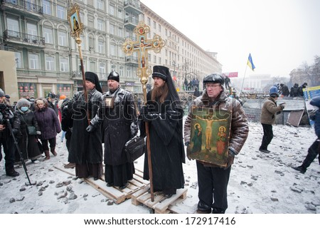 KIEV, UKRAINE - JAN 21: Snowfall on the winter street with crowd of activists and the priests of Ukrainian Orthodox Church at front of barricades on anti-government protest on January 21 2014 in Kyiv  - stock photo