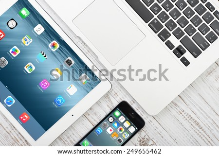 KIEV, UKRAINE - JANUARY 29, 2015: Apple iPhone 5s, iPad Air 2 and MacBook Air on table. Apple Inc. is an American multinational corporation that designs, develops, and sells consumer electronics. - stock photo