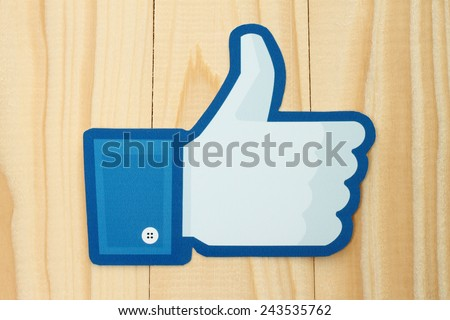 KIEV, UKRAINE - JANUARY 10, 2015: Facebook thumbs up sign printed on paper and placed on wooden background. Facebook is a well-known social networking service. - stock photo