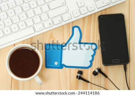 KIEV, UKRAINE - JANUARY 10, 2015: Facebook thumbs up sign printed on paper and placed on wooden background with coffee, keyboard and smart phone. Facebook is a well-known social networking service. - stock photo