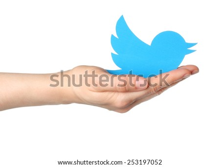 KIEV, UKRAINE - JANUARY 16, 2015: Hand holds twitter logotype bird printed on paper. Twitter is an online social networking service that enables users to send and read short messages. - stock photo