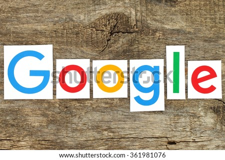 Kiev, Ukraine - January 12, 2016:New Google logotype printed on paper, cut and placed on old wood.Google is USA multinational corporation specializing in Internet-related services - stock photo