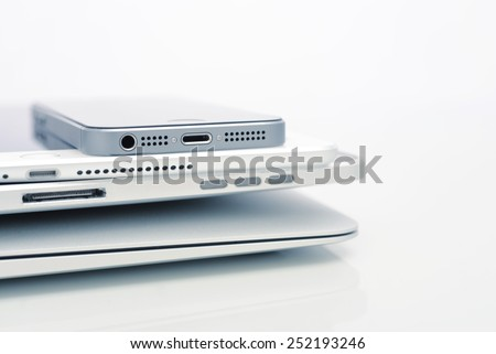 KIEV, UKRAINE - JANUARY 29, 2015: Pile of Apple iPhone 5s, iPad Air 2 and MacBook Air . Apple Inc. is an American multinational corporation that designs, develops, and sells consumer electronics. - stock photo