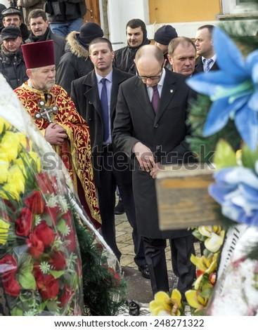 KIEV, UKRAINE - January 29, 2015: Prime Yatsenyuk laying flowers at the grave of heroes. -- Ukrainian politicinas attended the ceremony Kruty Heroes - stock photo