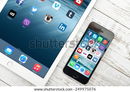 KIEV, UKRAINE - JANUARY 29, 2015: Social media apps on screen of iPad and iPhone. Social media are most popular tool for communication, sharing information and content between people in internet. - stock photo