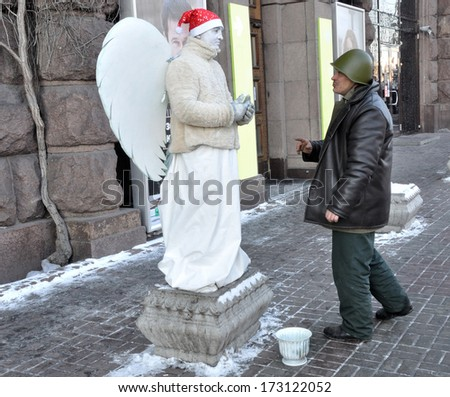 KIEV, UKRAINE - 24 JANUARY 2014: Unknown demonstrator talk with an angel during the civil protest in government district on January 24, 2014 in Kiev, Ukraine.