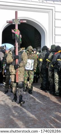 KIEV, UKRAINE -Â?Â? 25 JANUARY 2014: Unknown fighters carry the coffin with dead Ukrainian revolutionary hero Michail Zhiznevskij on January 25, 2014 in Kiev, Ukraine. - stock photo