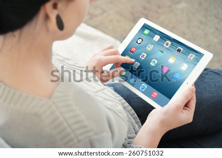 KIEV, UKRAINE - JANUARY 29, 2015: Woman working on a brand new white Apple iPad Air 2, 6th generation of the iPad, developed by Apple inc. and was released on October 16, 2014 - stock photo