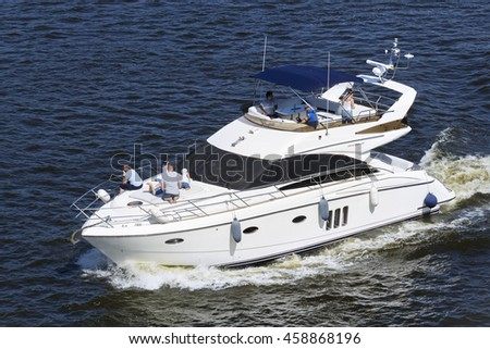 KIEV, UKRAINE - JULY 24, 2016: Closeup of a yacht with people on board sailing at high speed in Dnieper river, Kiev, Ukraine