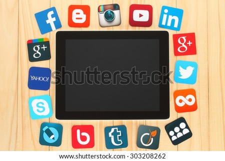 KIEV, UKRAINE - JULY 01, 2015: Famous social media icons such as: Facebook, Twitter, Blogger, Linkedin, Google Plus, Myspace and others. printed on paper and placed around iPad on wooden background. - stock photo