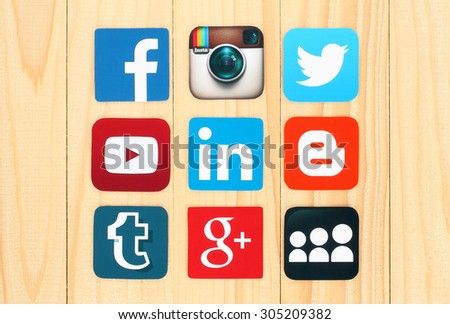 KIEV, UKRAINE - JULY 01, 2015: Famous social media icons such as: Facebook, Twitter, Blogger, Linkedin, Tumblr, Myspace and others, printed on paper and placed on wooden background. - stock photo