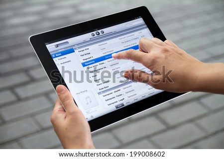 KIEV, UKRAINE - JULY 31, 2011:  Person choosing song in iTunes playlist on a brand new Apple iPad. iTunes app is the media library for download and organize media files, develop by Apple inc.   - stock photo