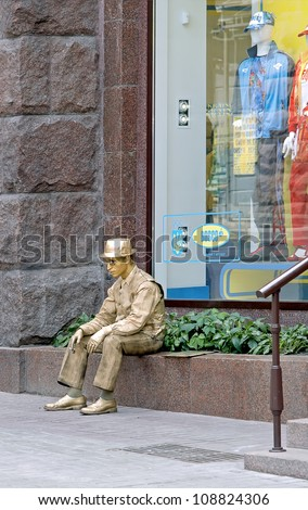 KIEV, UKRAINE - JUNE 30: An unidentified busking mime smoking performs on Khreshchatyk street in Kiev, Ukraine on June 30, 2012. Living golden statue is the entertainment for the tourists. - stock photo