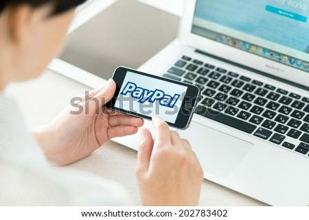 KIEV, UKRAINE - JUNE 27, 2014: Person holding a brand new Apple iPhone 5S with PayPal logo on a screen. PayPal is the worldwide e-commerce business service allowing payments and money transfers