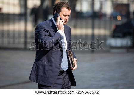 KIEV, UKRAINE - Mar. 11, 2015: Ukrainian Economy Minister Aivaras Abromavicius talking on the phone in front of Presidential Administration of Ukraine