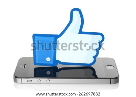 KIEV, UKRAINE - MARCH 7, 2015: Facebook thumbs up sign printed on paper and placed on iPhone on white background. Facebook is a well-known social networking service. - stock photo