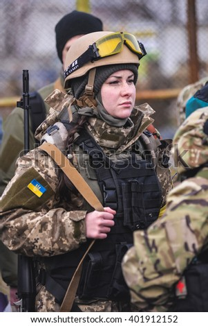 """KIEV,UKRAINE - March 26 : Girl with rifle on his shoulder in military uniform with bulletproof vest and helmet during military training for civilians """"RUH 100.Tryzub"""" in Kiev,Ukraine on March 26,2016. - stock photo"""