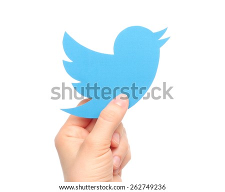 KIEV, UKRAINE - MARCH 7, 2015: Hand holds twitter logotype bird printed on paper. Twitter is an online social networking service that enables users to send and read short messages. - stock photo