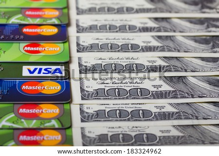KIEV, UKRAINE - March 22: Pile of credit cards, Visa and MasterCard, with US dollar bills, in Kiev, Ukraine, on March 22, 2014. - stock photo