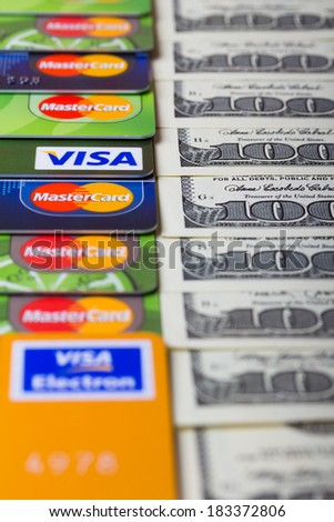 KIEV, UKRAINE - March 22: Pile of credit cards, Visa and MasterCard, with US dollar bills, in Kiev, Ukraine, on March 22, 2014. Selective focus. - stock photo