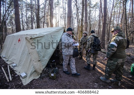 "KIEV,UKRAINE - March 26 : Volunteers in uniform near medical tent in forest during military training ""RUH 100.Tryzub"" for civilians in Kiev,Ukraine on March 26,2016."