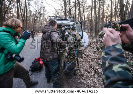 """KIEV,UKRAINE - March 26 : Wounded soldier is carried to an ambulance during first aid simulation on military training """"RUH 100.Tryzub"""" for civilians in Kiev,Ukraine on March 26,2016. - stock photo"""