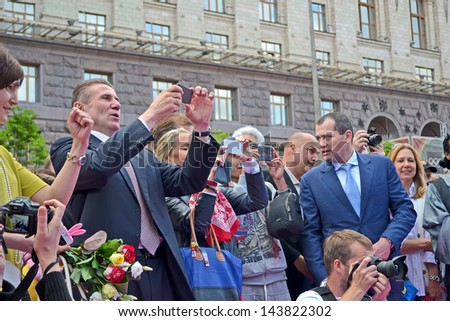 KIEV,UKRAINE-MAY 25: Celebration of 100th anniversary of 1st Russian Olympiad  in Kiev, Ukraine on May 25,2013. Ukrainian pole vaulter Sergey Bubka making photo by camera on Kreshatik street in Kiev. - stock photo