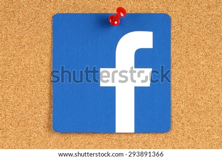 KIEV, UKRAINE - MAY 25, 2015: Facebook logo sign printed on paper and pinned on cork bulletin board. Facebook is a well-known social networking service - stock photo